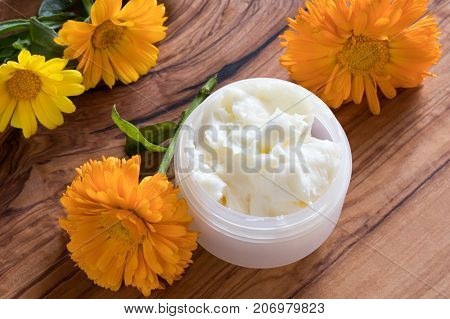 A Jar Of Calendula Cream, With Calendula Flowers In The Background