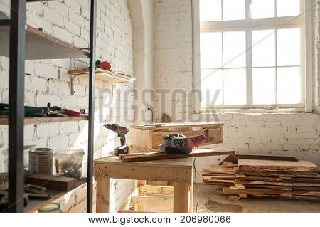 Joinery shop interior with tools and supplies, woodwork machines and equipment, instruments on workbench, starting small carpentry workshop business concept, making wooden ware, custom made furniture poster