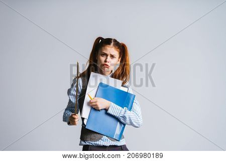 The lady-teacher in a strict suit looks into the camera and holds a pointer and a folder with documents