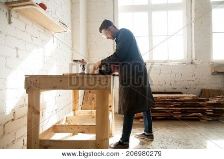 Joiner using electric tools while working in carpentry. Millennial worker getting on-the-job trailing in woodworking workshop, improve his skills in profession. Short-term job opportunities concept