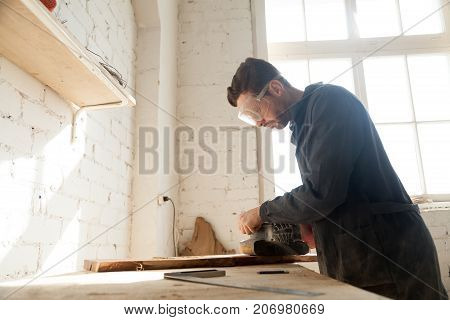 Carpenter in protective glasses polishes wooden board with handle belt sanding machine on workbench in workshop. Small business owner working in his manufacturing. Joiner made custom wooden furniture