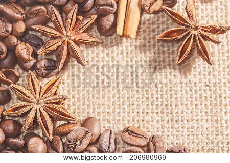 Design frame with coffee beans cinnamon stocks on sackcloth with spices anise. Closeup image.