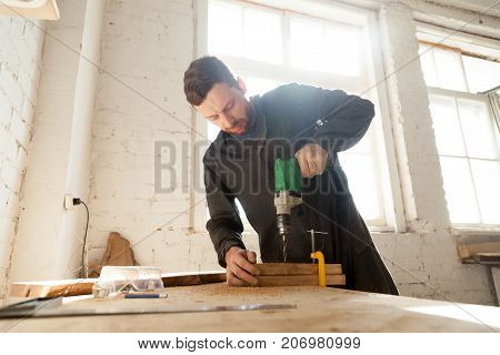 Skilled professional carpenter in workwear using electric drill machine, custom woodworking, making woodware, young experienced craftsman drilling wooden planks on table at workshop. Small business