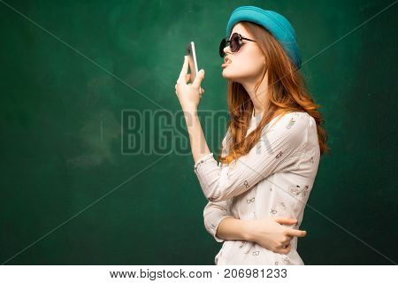 funny girl in a hat holds a phone in her hands and pokes her face on a green background