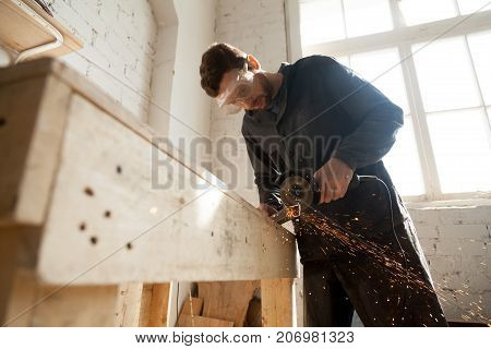 Worker in protective eyewear working in small workshop interior using die angle grinder for cutting steel bar, throwing sparks from metal grinding machine with abrasive disk wheel, making furniture