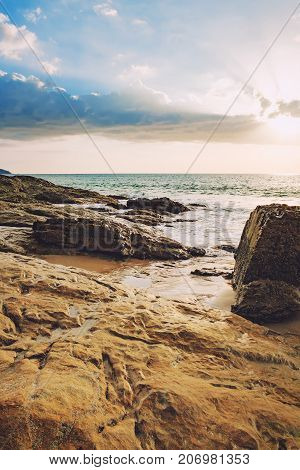 Beautiful seascape with sea and rock in Nang Thong Beach at sunset, Khao Lak, Thailand. View of bright blue sea with protruding stones in the foreground
