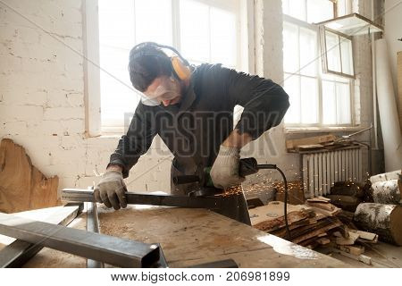 Young workman in protective equipment using angle grinder to smooth metal profile pipe in workshop interior with wooden planks and lumber. Focused on work skilled worker grinds steel parts with sparks