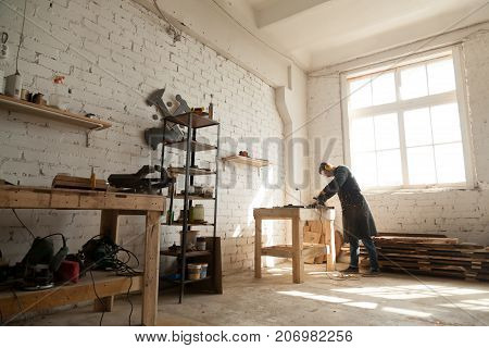 Skilled young workman wearing protective workwear working with steel metal parts of construction in own workroom with tools on shelves, self-employed manual worker starting small business repair shop