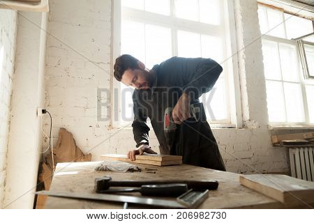Joiner drilling wooden boards on workbench with electric drill. Young carpenter makes custom cabinet, repairs antiquarian furniture, working in workshop. Part time small business opportunity concept