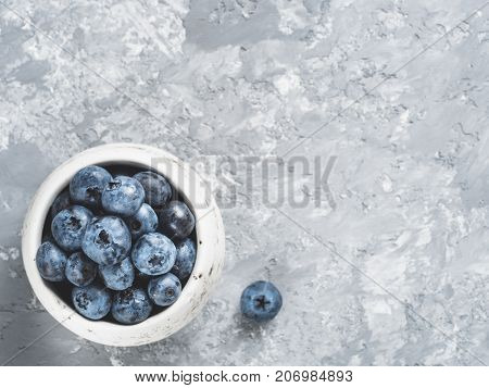 Blueberries on gray concrete background. Blueberry border design. Fresh picked bilberries in bowl close up. Copyspace. Top view or flat lay