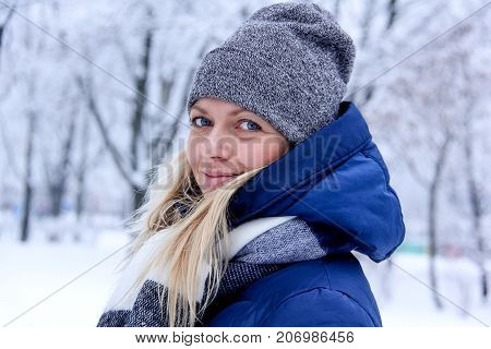 Beautiful winter portrait of young woman in the winter snowy scenery. Beautiful girl in winter clothes. Young woman portrait. beauty girl on the blurred background