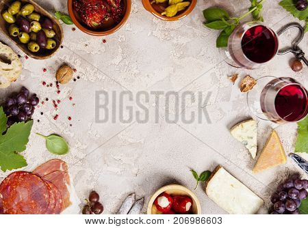 Wine and snack set. Variety of cheese, mediterranean olives, prosciutto,baguette slices, black and green grapes, sun-dried tomatoes, peppers and glasses of red wine over grey marble background