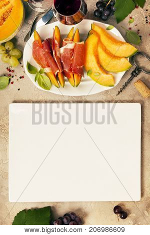 Prosciutto ham with cantaloupe melon, basil leaves and wine over grunge background. Top view, copy space