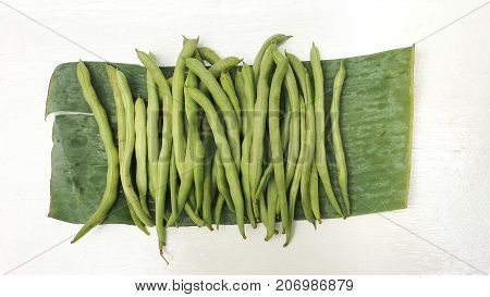 String bean raw vegetable on banana leaf photo top view isolate on white wood and clipping paths.