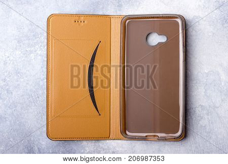 Brown leather case for smartphones flip-cover. Against a light background