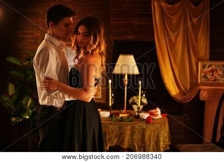 Couple dancing and kissing indoor. Romantic evening interior for loving couple. Happy people in love. Burn golden candle in foreground. Wedding night.