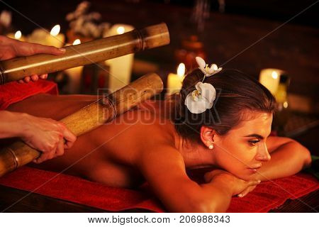 Bamboo massage of woman in spa salon. Girl on candles background in massage spa salon. Rest in an elite beauty salon. Female have relax big stick after sport on red towel. Close up of hands.