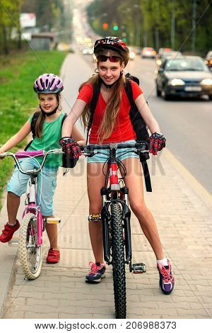 Bikes bicyclist girl. Girls wearing bicycle helmet with rucksack ciclyng bicycle. Girls children cycling meet on white bike lane. Bike share program save money and time at city street. poster