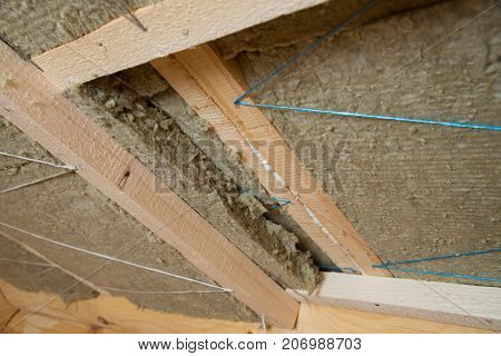 Roof heat isolation with mineral wool in wooden house, building under construction.