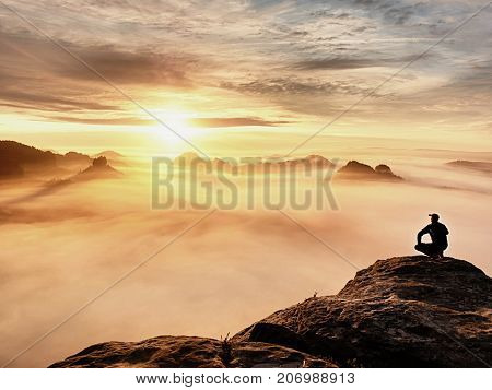 Tourist Sit On Peak Of Sandstone Rock And Watching Into Colorful Mist And Fog In  Morning Valley. Sa