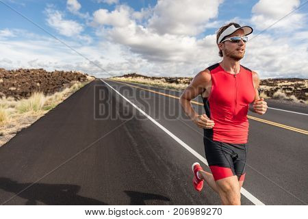 Runner fit athlete man running in triathlon suit training for Iron man on Hawaii. Fit male triathlete exercising endurance cardio on road.