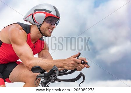 Triathlon biking man cyclist portrait riding bike. Male triathlete cycling on triathlon bike. Fit man professional athlete on triathlon bicycle wearing time trial helmet for ironman race.