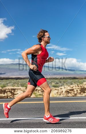 Triathlon runner triathlete man running in tri suit at ironman competition race on road. Sport athlete on marathon run training exercising cardio in professional outfit for triathlon. Fitness, Hawaii