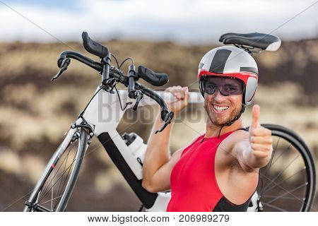 Triathlon biking - male triathlete cycling giving thumbs up success hand sign cheering happy excited at camera. Fit man cyclist on professional triathlon bicycle for ironman race. Big Island, Hawaii.