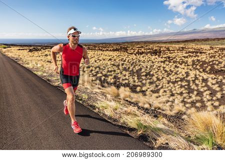 Sport runner man athlete running in triathlon suit training for Iron man on Hawaii. Fit male triathlete exercising on road in nature landscape on Big Island, Hawaii.