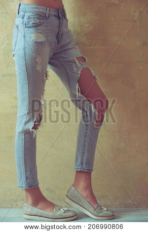 Ripped jeans female feet. Gorgeous girl in torn jeans over studio background. Lady in fashionable ripped jeans stands in gray wall. Sexy young woman in trendy clothes on a grunge background