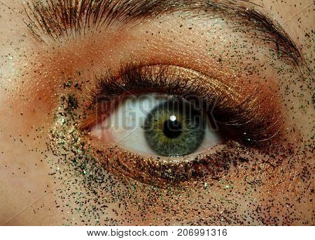 Unusual eye with creative make-up with sparkles. Open green eye close up. Female pupil and healthy lens eyesight and eye health. Gold and shine in cosmetology