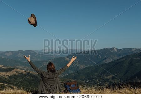 Sitting Young Woman Traveler Tosses A Hat Against The Background Of The Mountains.  Freedom Concept