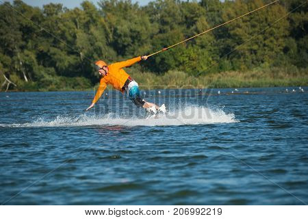 Wakeboarder, In Orange Shirt, Turns By Hand Touching Water Spray