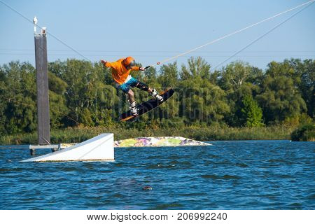 Wakeboarder, In Orange Shirt And Helmet, Is Jumping