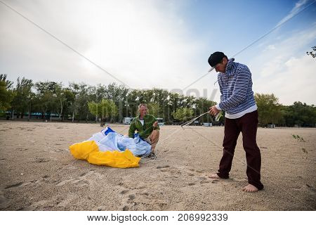 Two Focused Men Lay Out A Kite, Paraglider