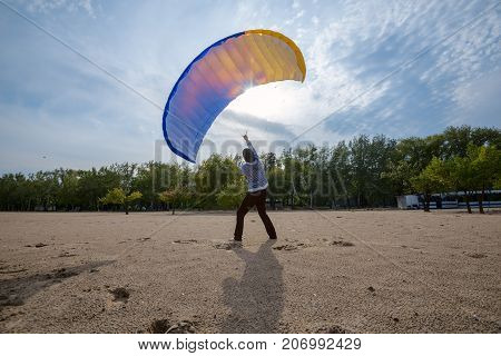 Man Struggles With The Wind, While Training With A Paraglider