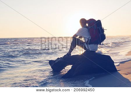 Traveler With Backpack Sits Next To Sea