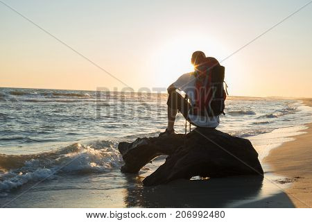 Man Traveler With Backpack Sits In The Surf