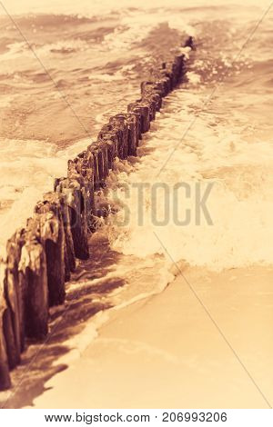 Retro vintage sepia image of an old wooden breakwaters on the Baltic coast beach