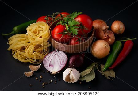 Vegetables and pasta on a black background