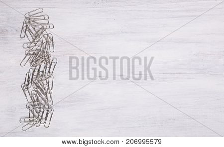 Line of many silver metal clips on wooden white background