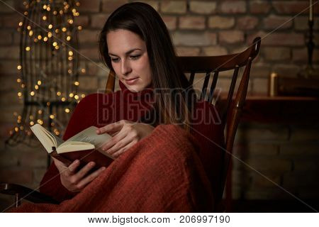 Young woman reading a book at wintertime in cosy home.