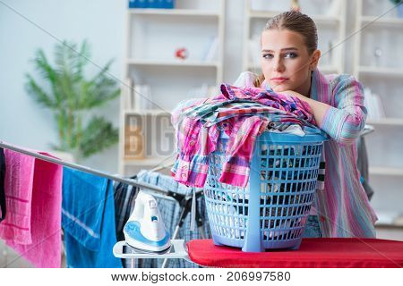Tired depressed housewife doing laundry