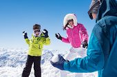 Happy son and smiling mother playing in the snow with father. Young family playing snowball fight in snowy mountain. Family having fight with snowballs during winter vacation. poster