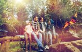 hike, travel, tourism and people concept - happy family sitting on bench and talking at camp near campfire in woods poster