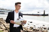 Happy purposeful businessman reading newspaper and enjoying stroll on shore. Cheerful handsome young man looking into distance and contemplating landscape. Ambition concept poster