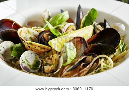 Exquisite Serving White Restaurant Plate of Spaghetti Nido with Sea Shells in Wine Sauce, Basil, Parsley and Celery Top View. Homemade Italian Vongole Clams Linguini Pasta on Black Marble Table