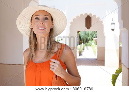 Stunning woman in bright dress exploring Moroccan riad poster
