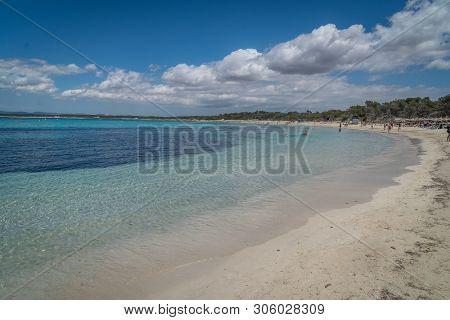 Wide Curving Sandy Tropical Beach With Beachgoers And Tourists Enjoying The Sunshine And Calm Blue O