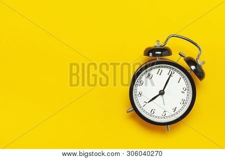 Black Retro Alarm Clock On Yellow Background Top View Flat Lay Copy Space. Minimalistic Background,